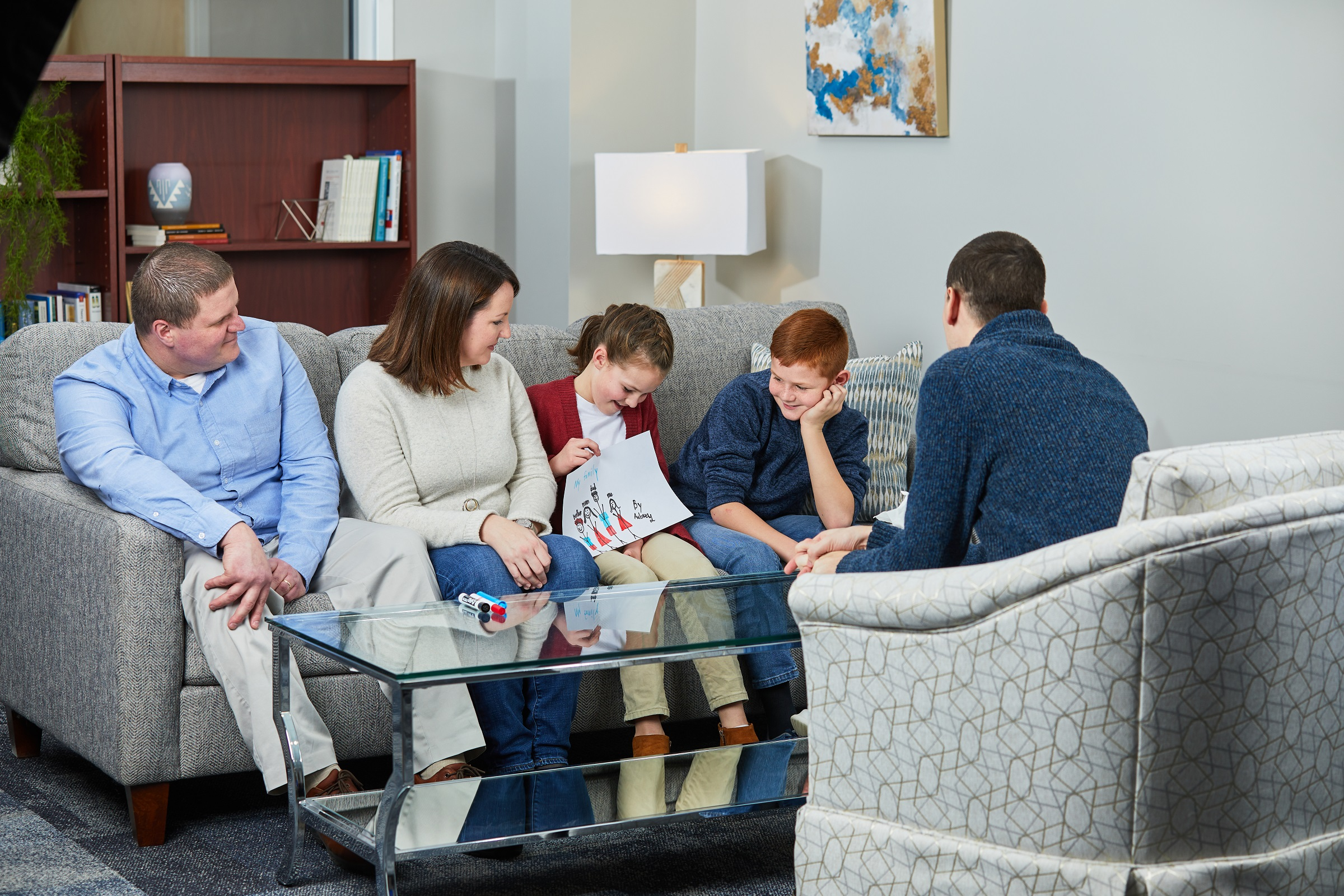 Caucasian family of four in a counseling setting with a male counselor. Son and daughter are drawing family pictures.